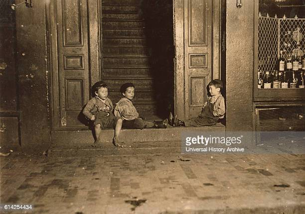 Three Young Children Hanging Out in Doorway Late at Night, Boston, Massachusetts, USA, circa 1909.