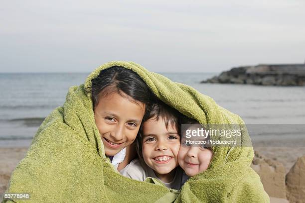 Three young children in towel on beach