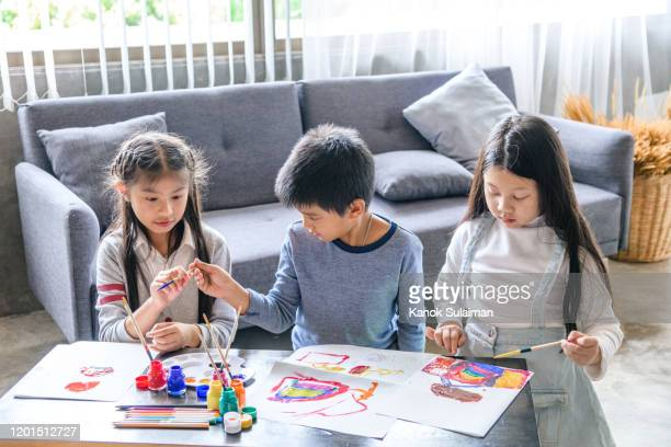 three young children painting and drawing in living room - sister stock pictures, royalty-free photos & images