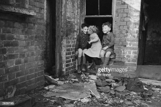 Three young children play in a bombdamaged building in the East End of London an area which London County Council plans to regenerate under its...