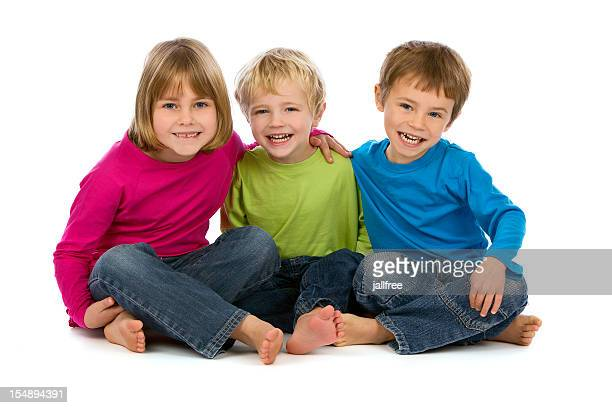 Three young children smiling on white background