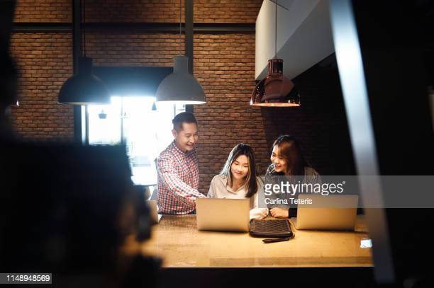 three young colleagues working together in an office - employee engagement stock pictures, royalty-free photos & images