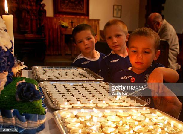 Three young Everton FC fans light candles at St Luke's Church at Everton FC Football grounds to pay their respect to eleven year old Rhys Jones who...
