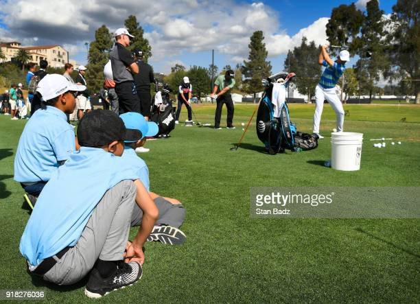 Three young fans watch Jordan Spieth hit tee shots on the driving range during the ProAm round for the Genesis Open at Riviera Country Club on...