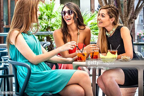 Three young fashionable female friends having cocktails at sidewalk cafe, Cagliari, Sardinia, Italy