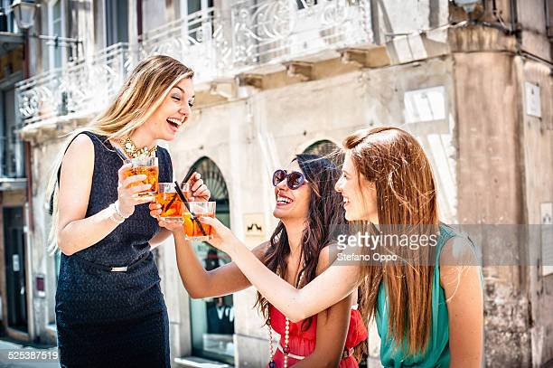 Three young fashionable female friends toasting with cocktails at sidewalk cafe, Cagliari, Sardinia, Italy