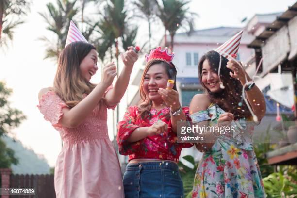 trois jeunes adultes féminins célébrant un événement - celebratory event photos et images de collection