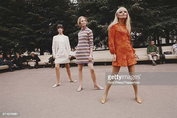 Three young female British fashion models pose wearing fashionable mini dresses in a square in a park in Moscow Russia in September 1967 The models...