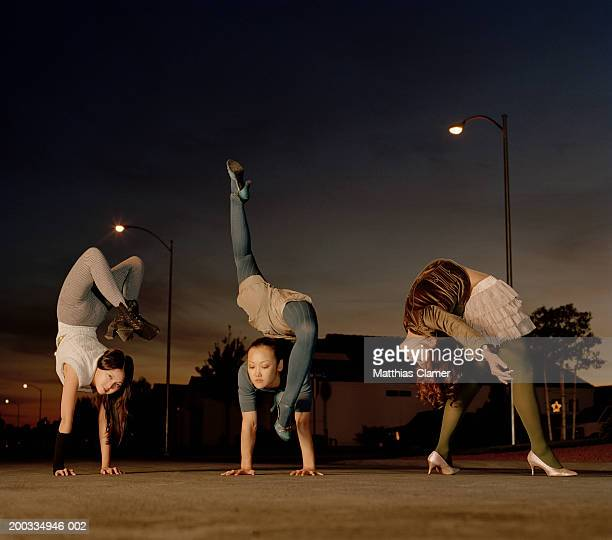 three young female contortionists practicing on road, dusk - contortionist stock pictures, royalty-free photos & images
