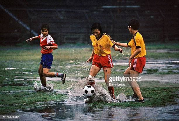 Three young female football players kick a ball around in heavy rain in Cam Pha northern Vietnam Their families work in the coal mines nearby