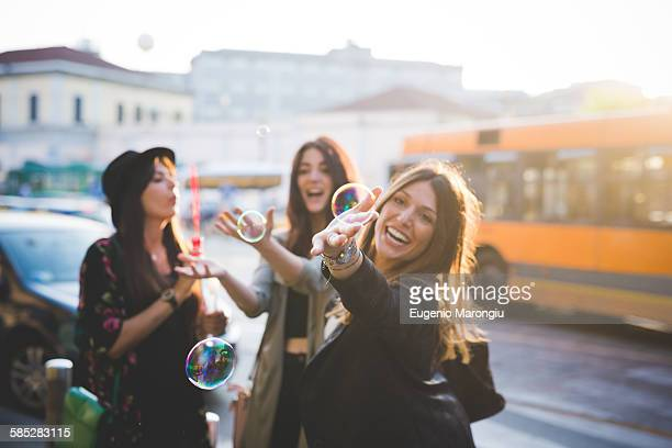 Three young female friends blowing bubbles on city street