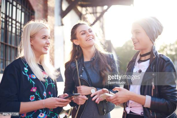 Three young female friends chatting on sunlit city street