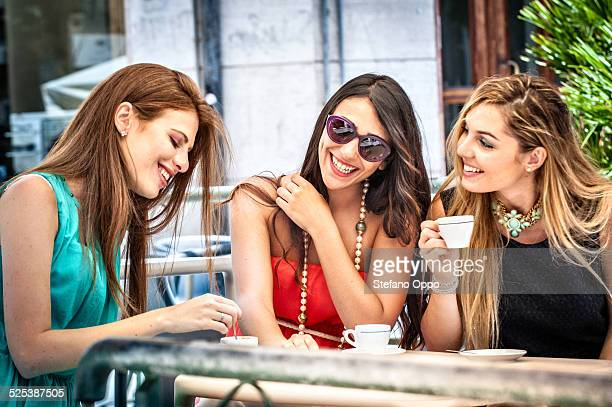 Three young female friends drinking espresso at sidewalk cafe, Cagliari, Sardinia, Italy