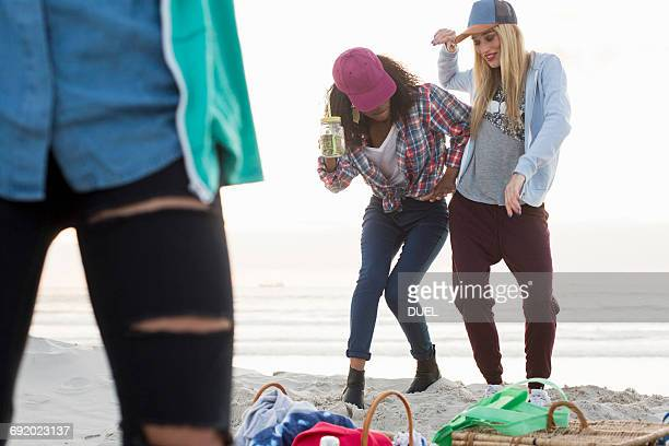 three young female friends fooling around at beach picnic, cape town, western cape, south africa - 18 19 años fotografías e imágenes de stock