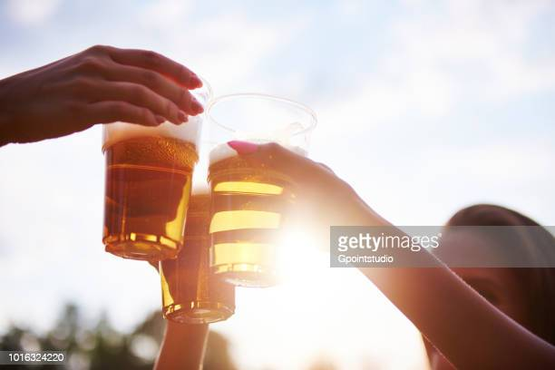 three young female friends making a toast with glasses of beer at holi festival - ビール ストックフォトと画像