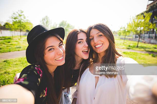 Three young female friends posing for selfie in park