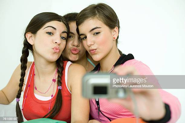 Three young female friends puckering as one takes photo with digital camera