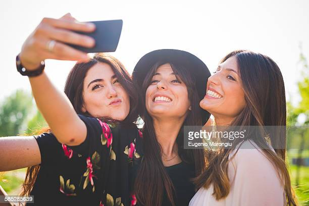 Three young female friends taking smartphone selfie in park