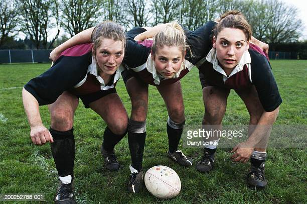 Three young female rugby players, crouching by ball, portrait