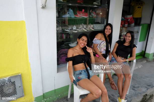 Three young female shop vendors sit outside with their smartphones in hand enjoying the first Christmas of peace after signing of the treaty which...