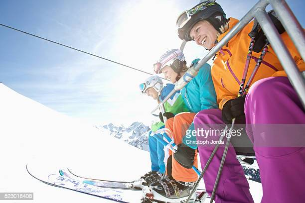 Three young female skiers sitting in ski lift