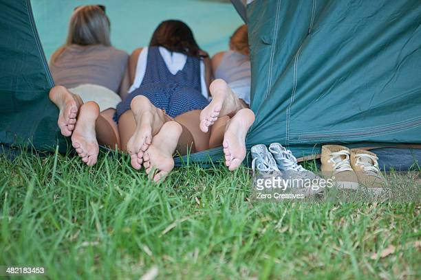three young females friends feet at tent entrance - woman lying on stomach with feet up stock photos and pictures
