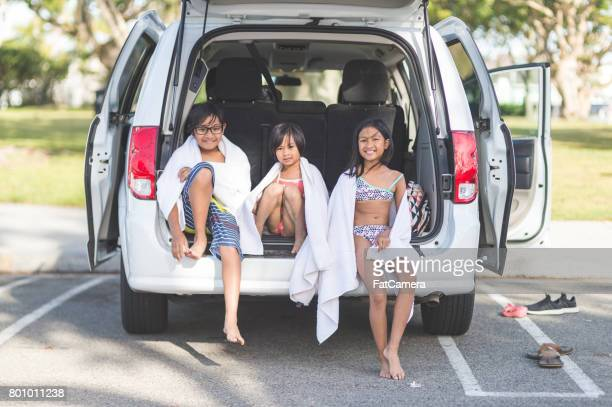 Three young Filipino children sitting on back of their vehicle and enjoying their time together after a day at the beach