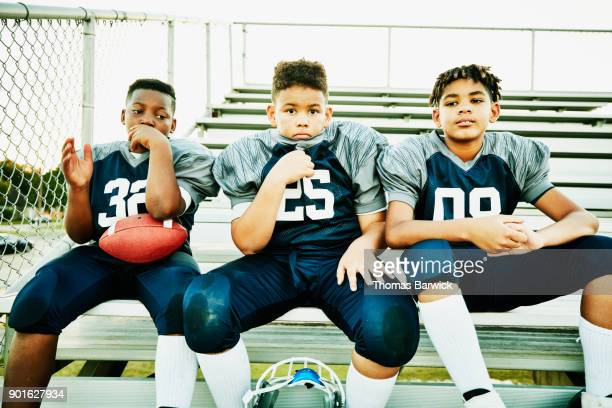 Three young football teammates sitting together on bleachers after football game