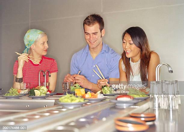 Three young friends eating at sushi bar, smiling