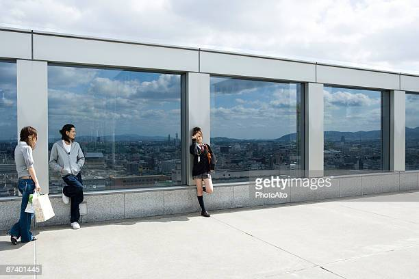 Three young friends leaning against glass wall overlooking city, Kyoto, Japan