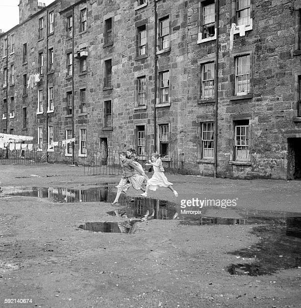 Three young friends leap over a puddle outside a Govan tenement block in Glasgow. September 1956
