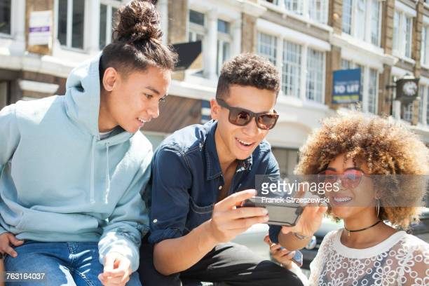 three young friends outdoors, looking at smartphone - generation z stock photos and pictures