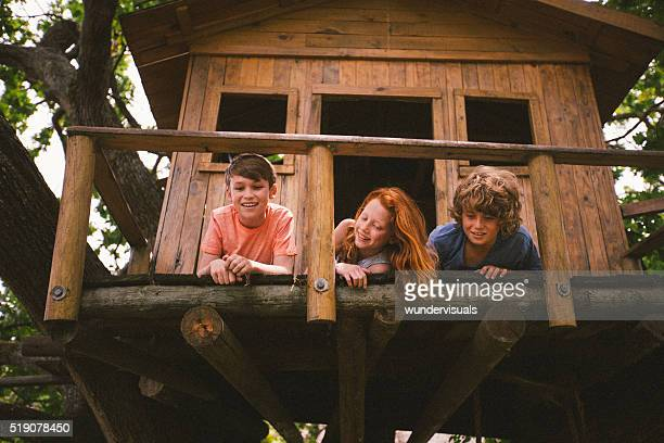 three young friends playing in a treehouse in summer - tree house stock pictures, royalty-free photos & images