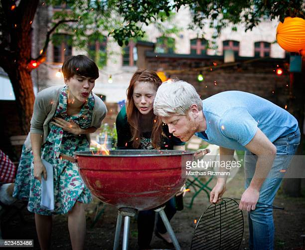 Three young friends preparing barbecue grill at garden party