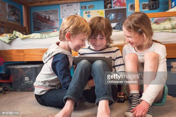 three young friends sharing a tablet computer - pre adolescent child stock pictures, royalty-free photos & images