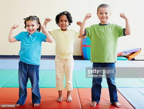 Three Young Friends Showing Off Their Muscles in a Nursery
