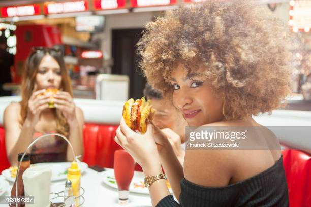 Three young friends, sitting in diner, eating burgers