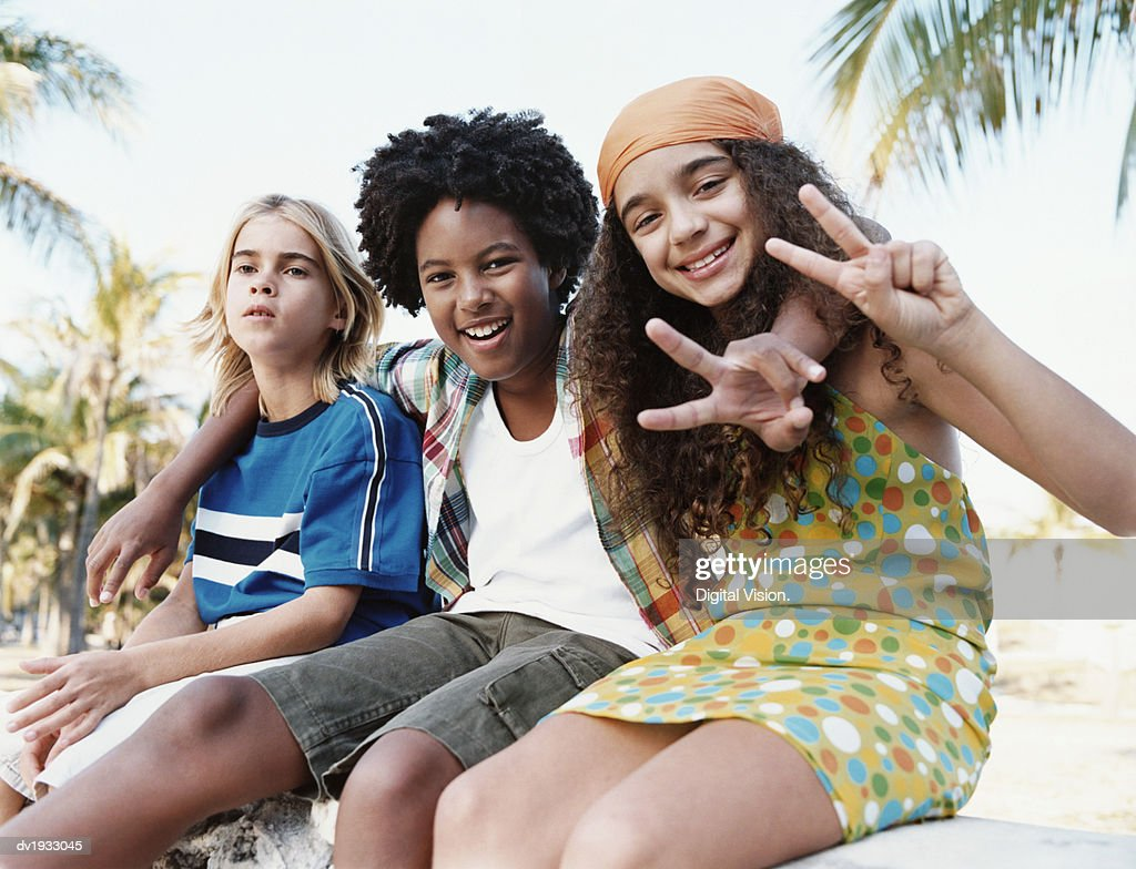 Three Young Friends Sitting Together on a Stone Wall Making Peace Signs : Stock Photo