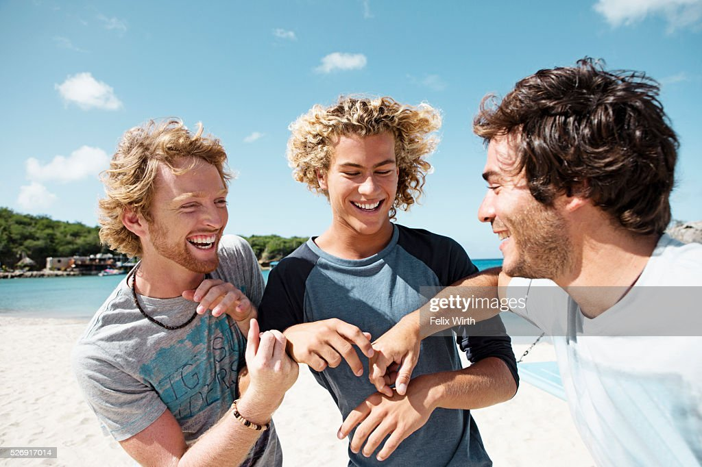 Three young friends smiling on beach : ストックフォト