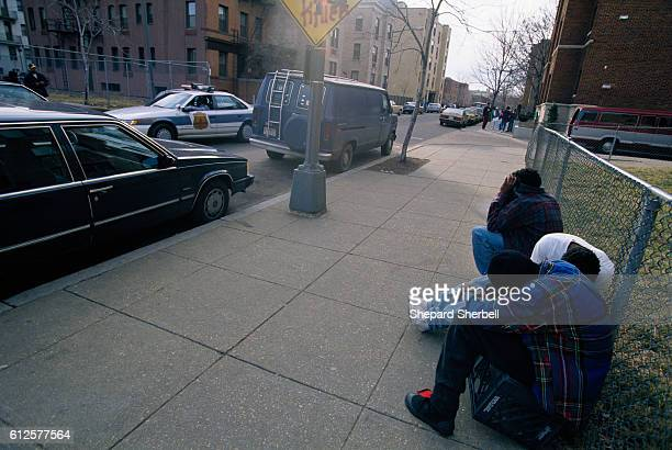 Three young gang members lower their heads and hide their faces in their shirts as a patrol car drives down a street in a poor section of Washington...