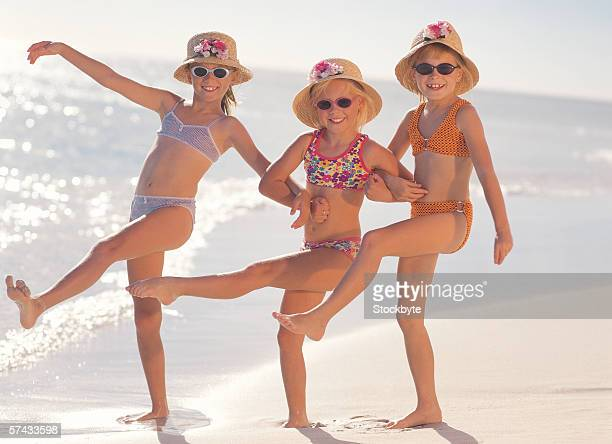 three young girls (4-6) dancing on the beach