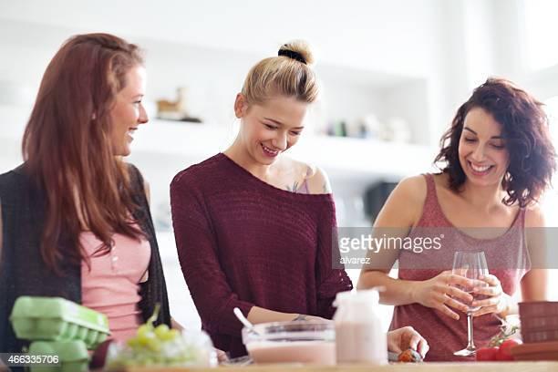 Three young girls having fun while preparing food in kitchen