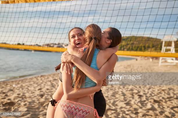 trois jeunes filles étreignant excité pour gagner le jeu de volley de plage - beach volley photos et images de collection