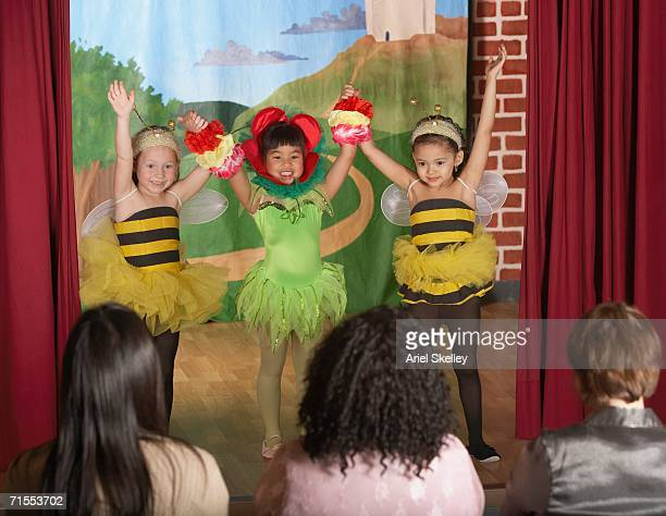 Three young girls in bee and flower costumes on stage