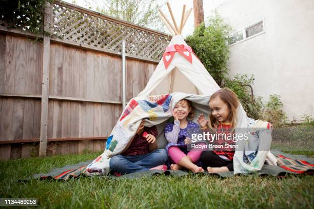 three young girls in garden hiding under blanket - teepee stock pictures, royalty-free photos & images