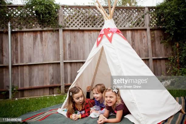 three young girls lying in teepee in garden - kampeertent stockfoto's en -beelden