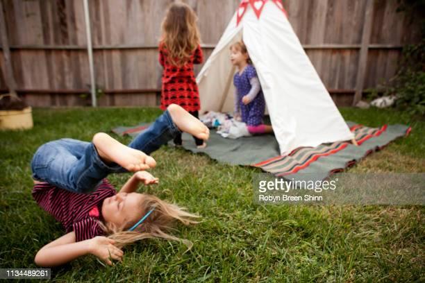 three young girls playing in garden - kampeertent stockfoto's en -beelden