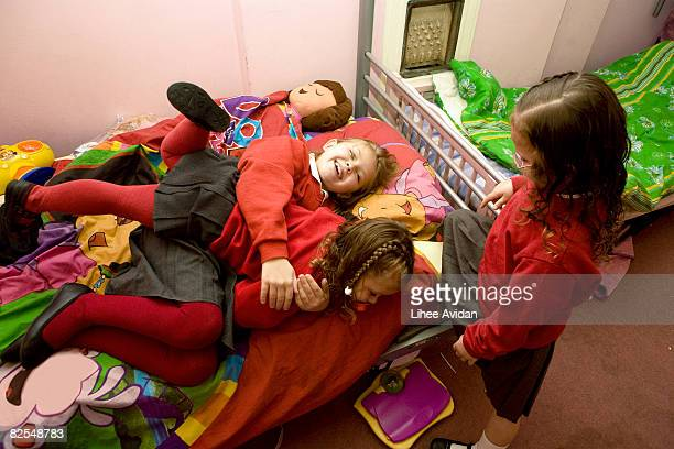 Three young girls playing on bed