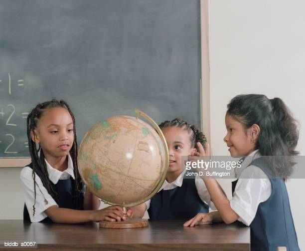 Three young girls playing with a globe in class