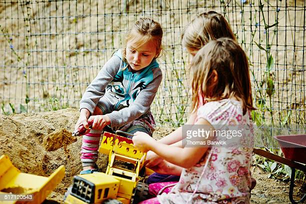 Three young girls playing with trucks in sandbox